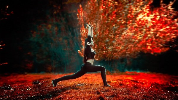 A woman practising yoga in a red forest.