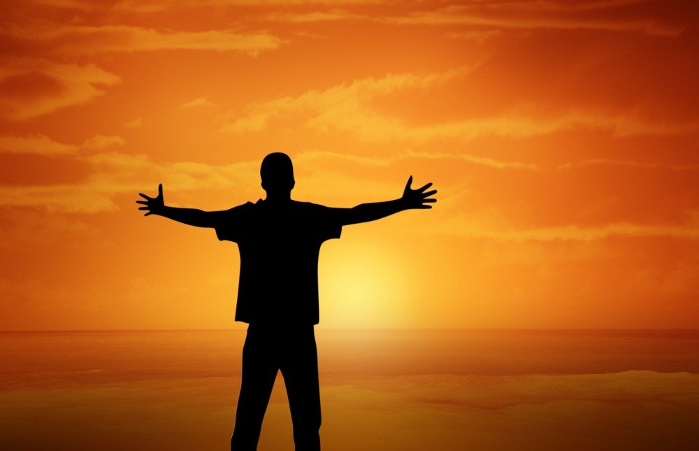 A man silhouetted against an orange sunset, embracing the sensory experience.