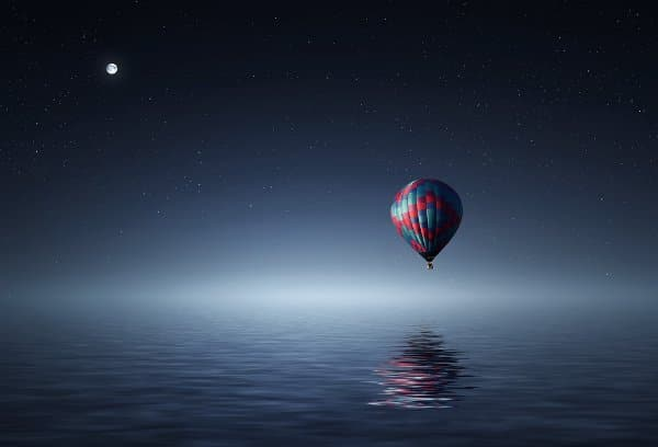 A hot air balloon hovers over a serene lake