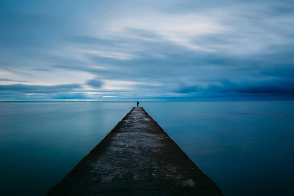 A simple pier leads out over water. A small silhouetted person stands at the end, looking out over the water and a cloudy sky, which have a merging blue / grey colour,