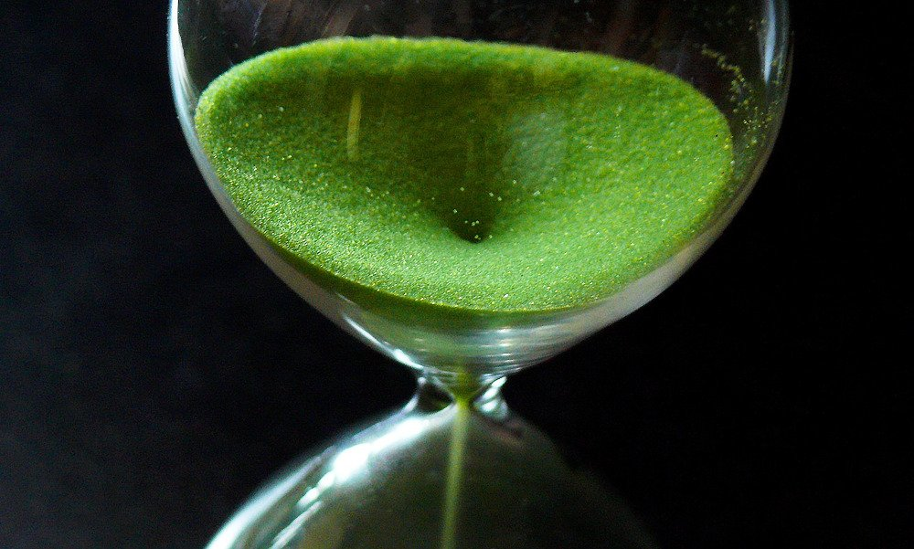 An hourglass seen from above with green sand pouring through, against a black background. This is time to relax.